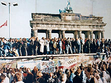 The Berlin Wall during its fall in 1989, with the Brandenburg Gate in the background.
