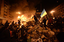 Euromaidan. State flag of Ukraine carried by a protester to the heart of developing clashes in Kiev. Events of 18 February 2014. Before the Overthrown of the Pro-Russian government