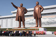 North Koreans bowing in front of statues of Kim Il-sung (left) and Kim Jong-il