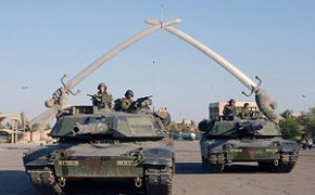"""U.S. Army M1A1 Abrams tanks and their crews pose for a photo in front of the """"Hands of Victory"""" monument at Baghdad's Ceremony Square in November 2003."""